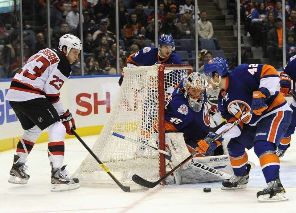Islanders goalie Anders Nilsson and Dylan Reese defend