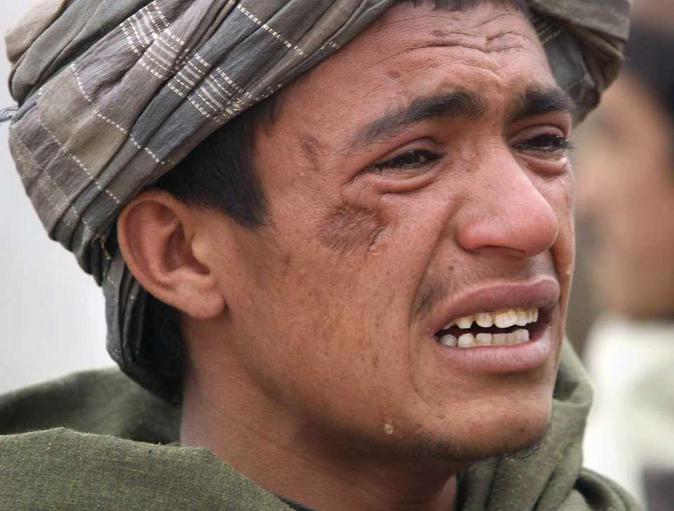An Afghan youth mourns Sunday for relatives who
