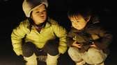 Children sit beside lighted candles in a memorial