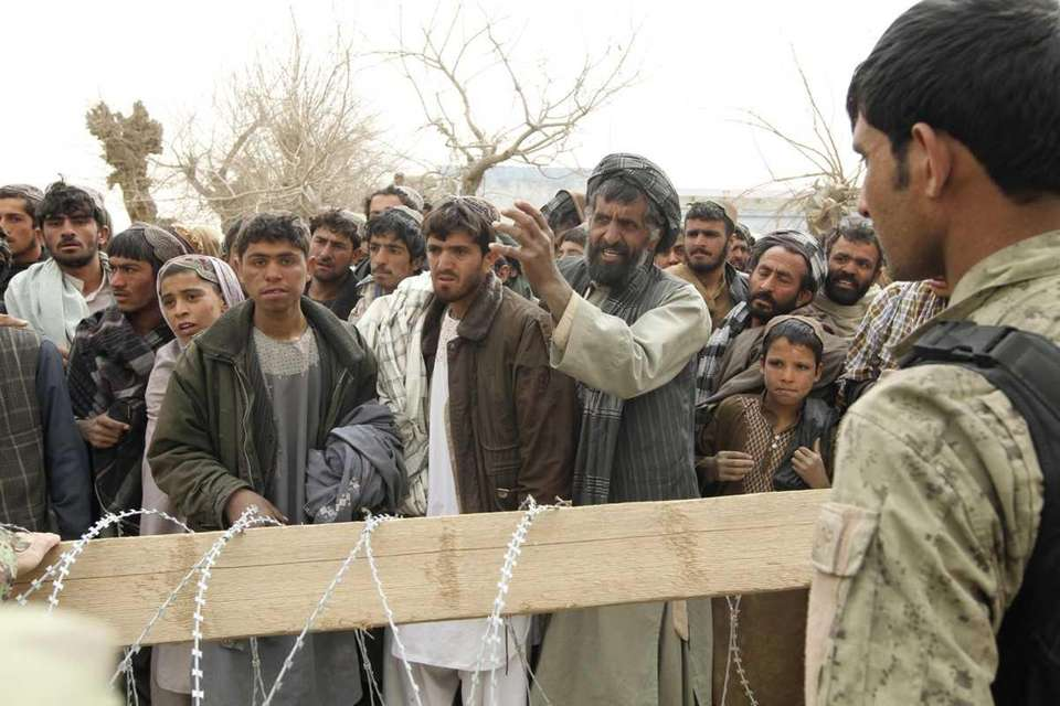 An Afghan soldier speaks to civilians gathered Sunday