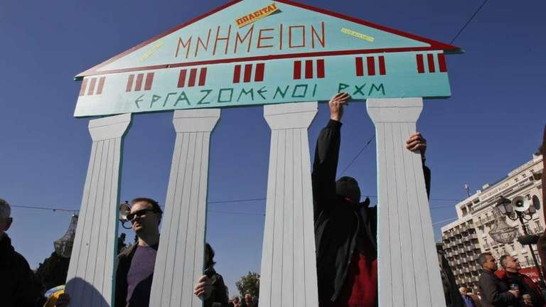 Protesters in Athens hold a sign that reads