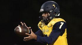 Xavier Arline, Shoreham-Wading River quarterback, takes a snap
