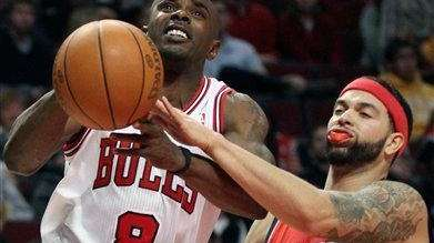 Chicago Bulls guard Mike James, left, is fouled