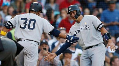 The Yankees' Edwin Encarnacion, left, celebrates his two-run