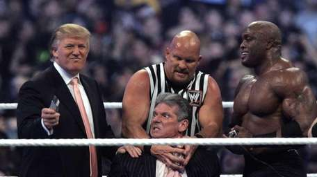 WWE Chairman Vince McMahon, center, held by