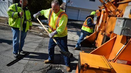 A Hempstead Town highway worker fills a pothole