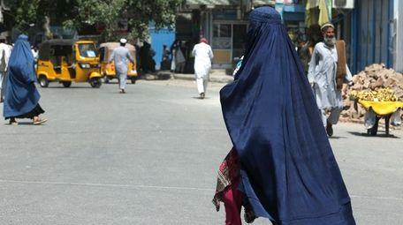 An Afghan woman walks down a road in