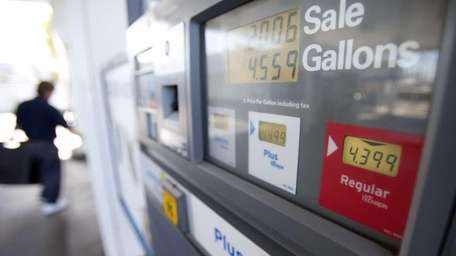 A man passes a gas pump showing the
