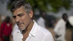 George Clooney stands outside a polling station on