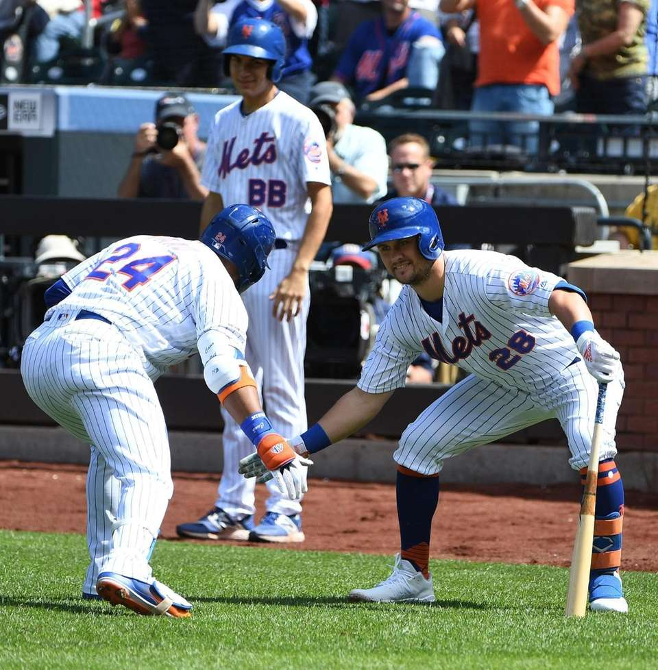 The Mets' J.D. Davis greets Robinson Cano after