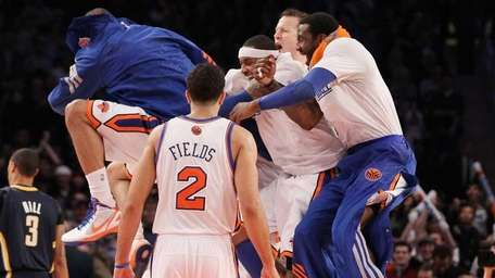 The Knicks celebrate after a three-point basket by