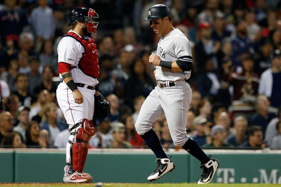 The Yankees' Mike Tauchman, right, scores in front