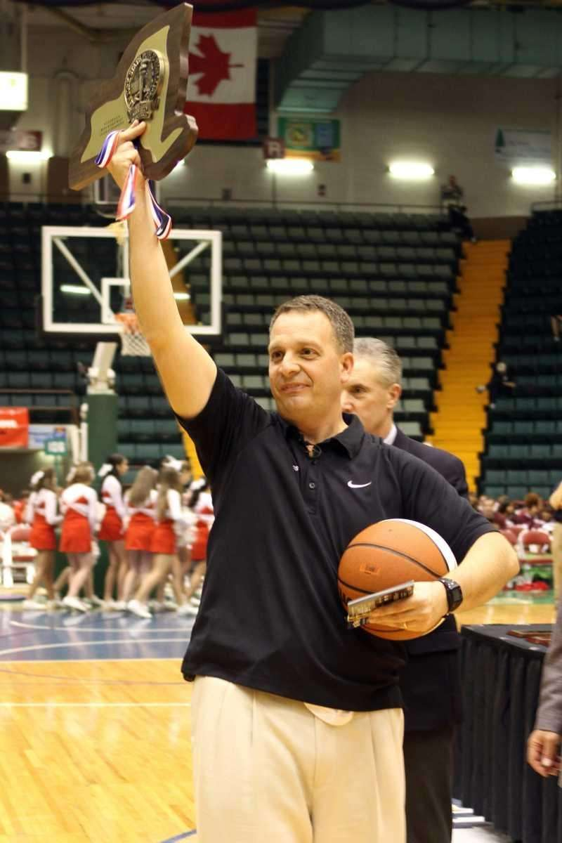 Harborfields coach Chris Agostino holds up the championship
