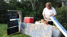Kelly Lester re-stocks her self-serve clam stand on