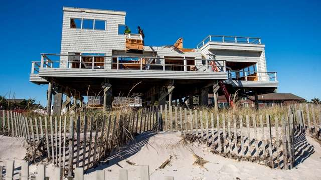 Workers dismantled oceanfront homes along Traffic Avenue in