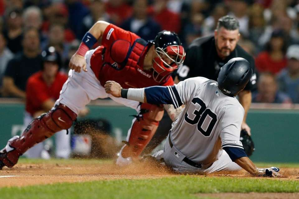 The Boston Red Sox's Christian Vazquez, left, lays