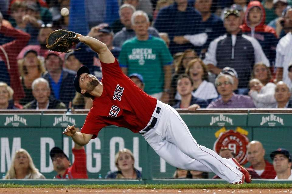 The Boston Red Sox's Sam Travis catches a