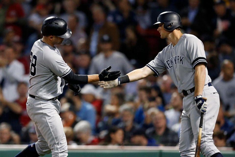 The New York Yankees' Austin Romine, left, celebrates