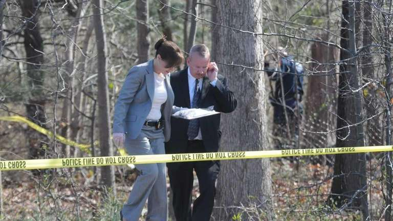 Investigators comb through the wooded area on Indian
