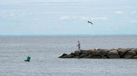 A lone fisherman on the jetties near Mattituck