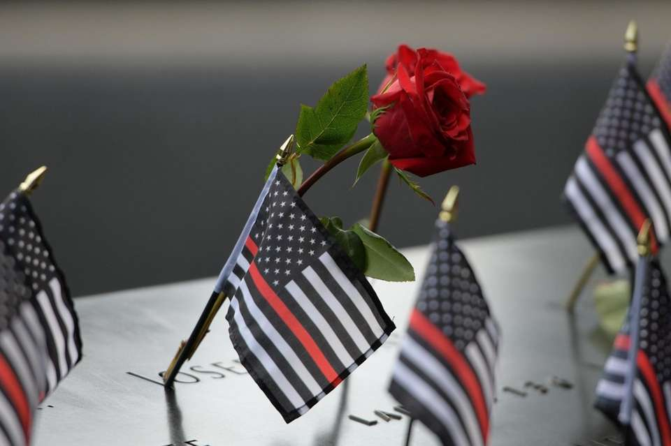 Flowers and flags are left honoring those who