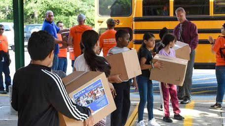 Students from Loretta Park Elementary School help unload