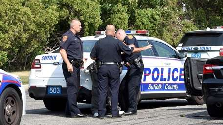 A woman is arrested in a parking lot