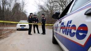 Police gather at the entrance to Manorville Hills