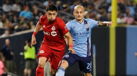 Toronto FC's Marco Delgado, left, fights for control