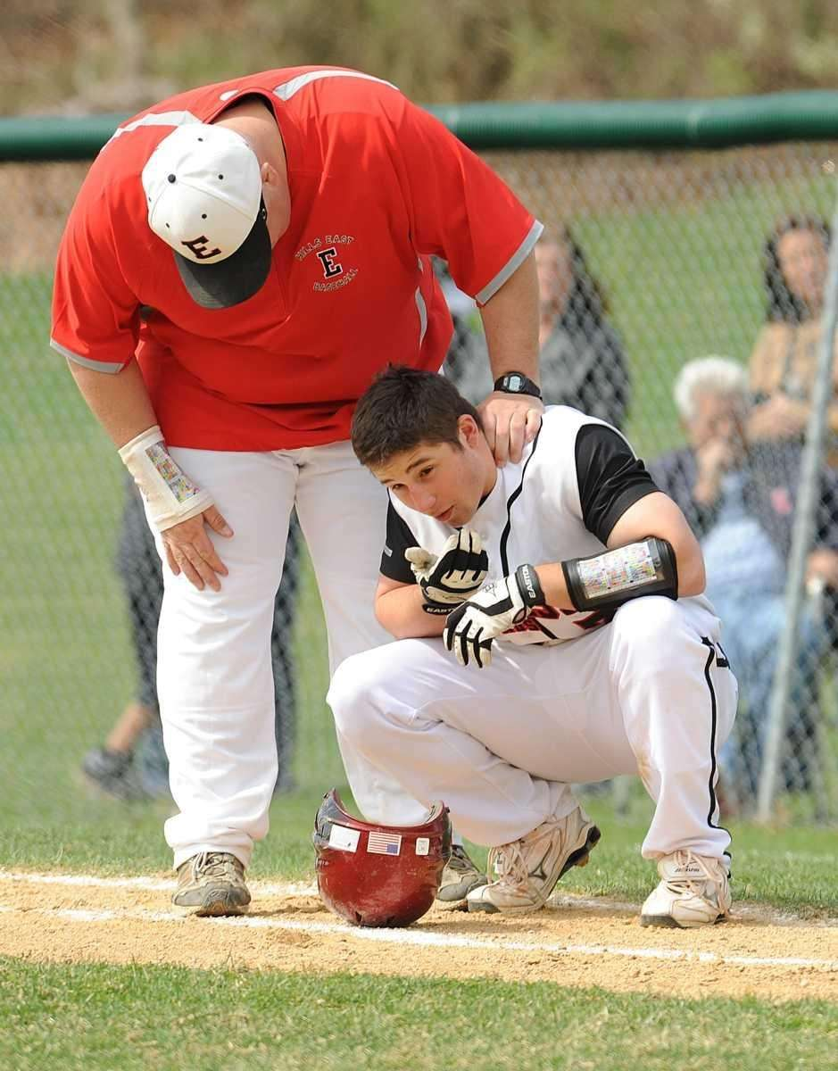 A coach checks on Hills East batter #7
