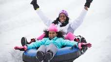 A pair of snow tubers cruises down the