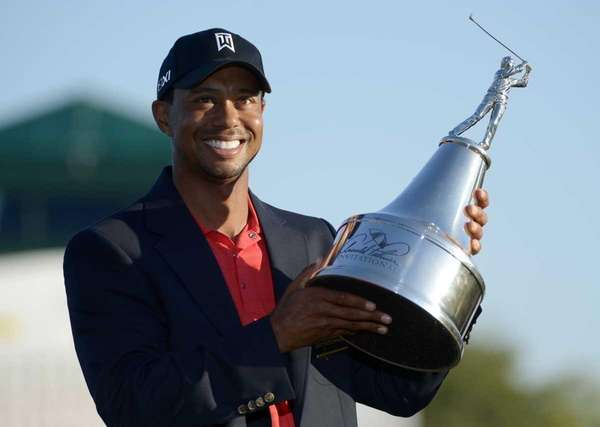 Tiger Woods hoists the championship trophy after winning