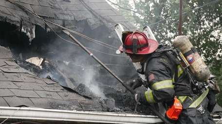 A firefighter battles a blaze at a home