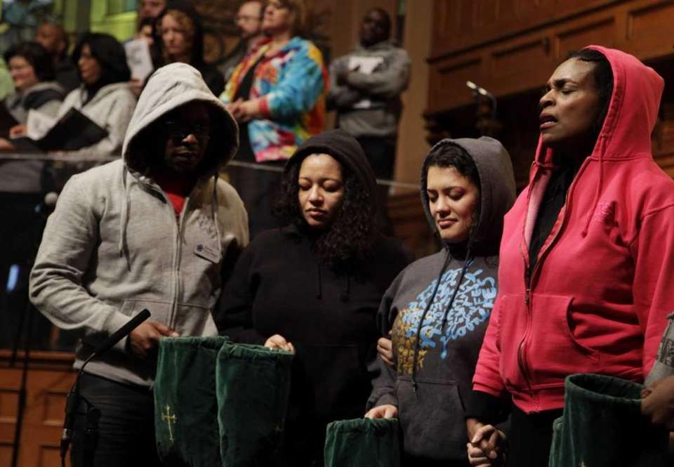 Senior Minister Jacqueline Lewis, right, prays with other