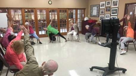 Senior citizens attend the chair yoga class at