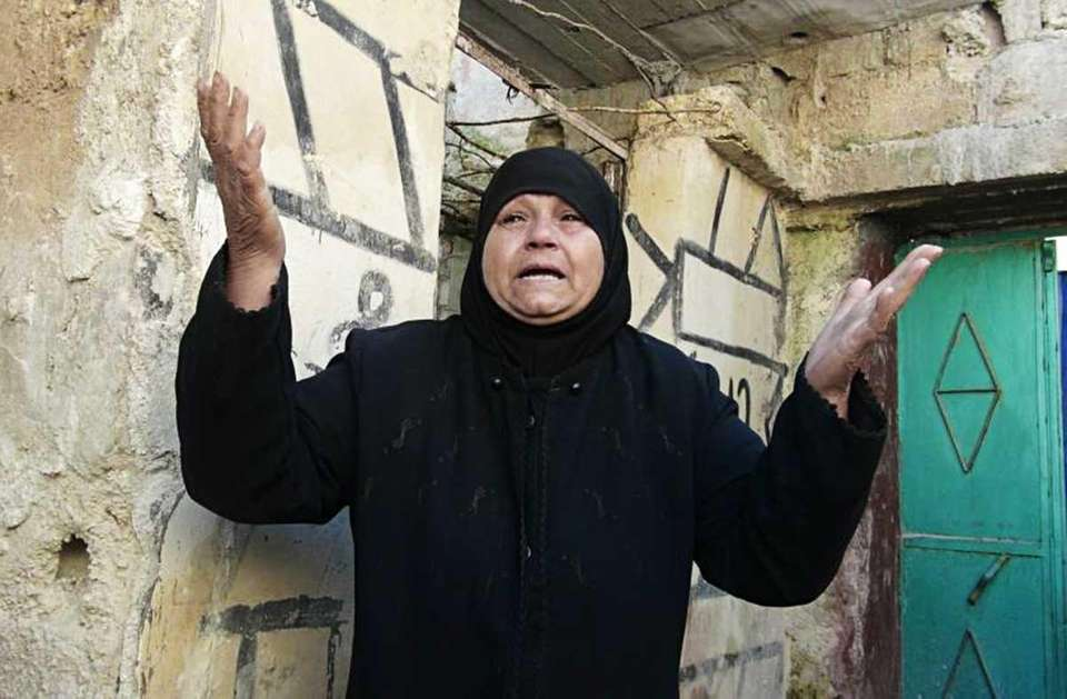 A Syrian woman reacts outside her house which