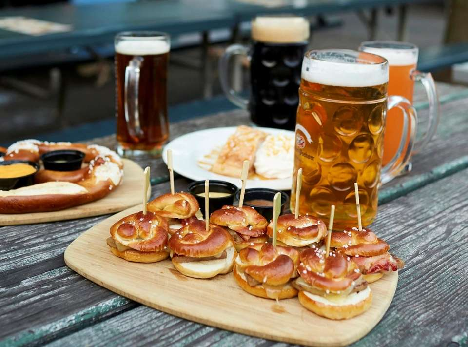 Mini pretzel slider rolls filled with sliced brats,