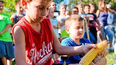 Kids race to husk an ear of corn