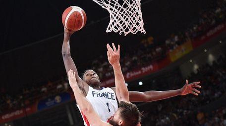 TOPSHOT - France's Frank Ntilikina (L) shots past