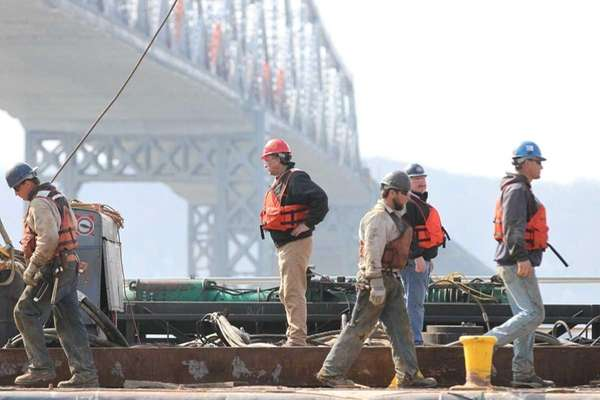 Workers continue early construction of pilings from barges