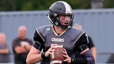 Commack QB Aiden McCarty rolls to the outside,