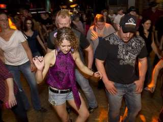 Customers do country line dances to music performed