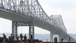Workers continue early construction of pilings, from barges,