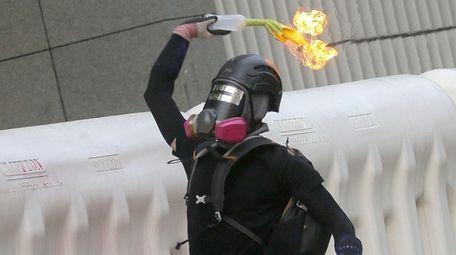 A protester throws a Molotov cocktail during an