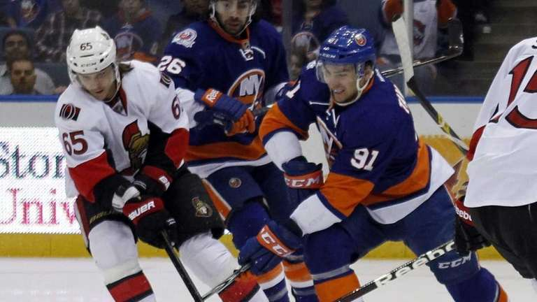 The Islanders' John Tavares battles for the loose