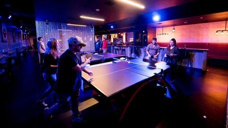 Patrons play ping pong at Smash, a new