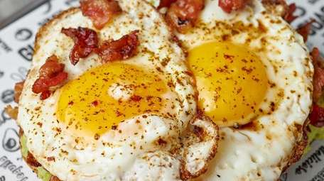Avocado toast topped with eggs and bacon at