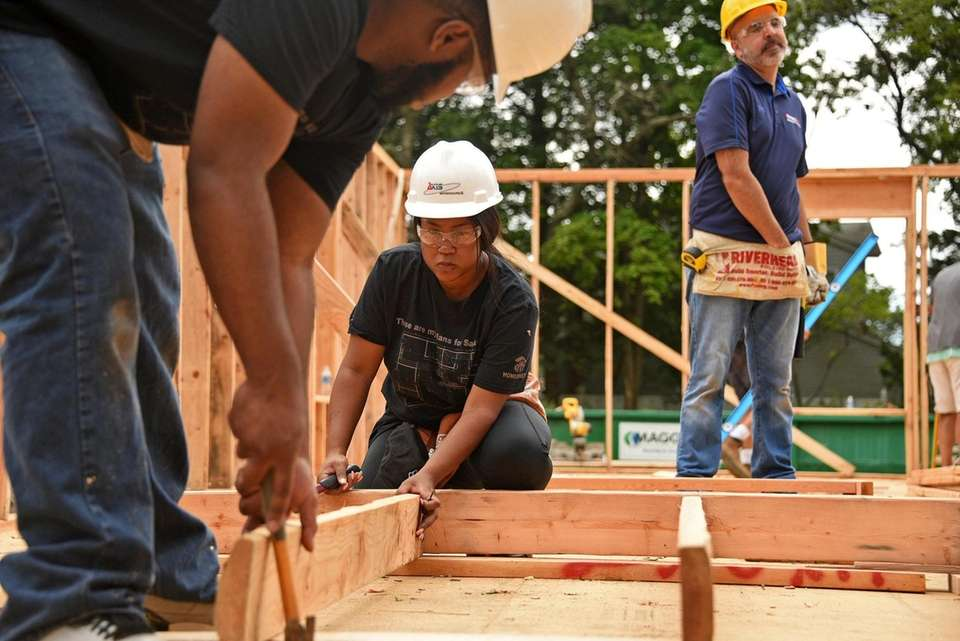 Darriell Morning, center, helps build the Wheatley Heights