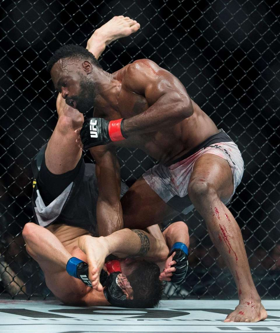 Middleweight fighters Uriah Hall, top, fights Antonio Carlos