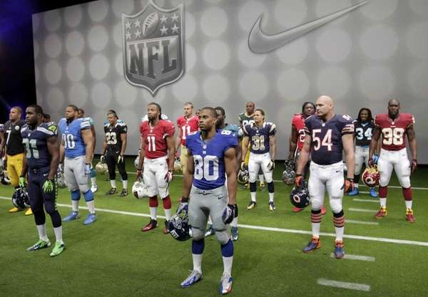 NFL players stand in their new uniforms during